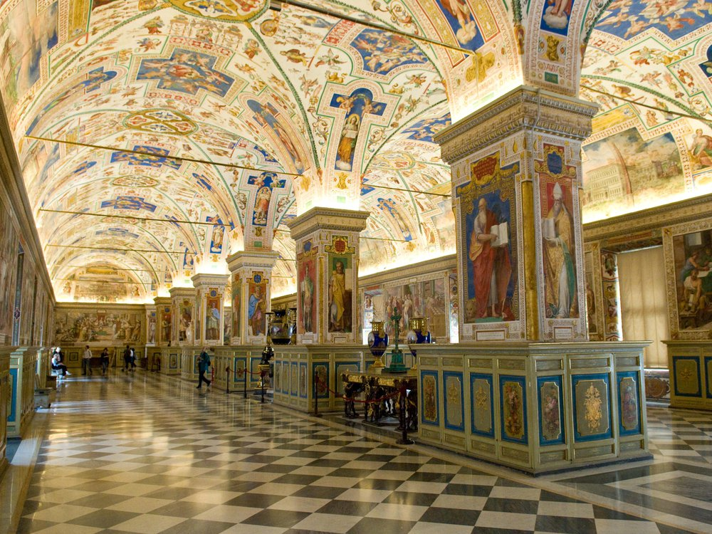 An ornately decorated hall with black and white checkered floors and depictions of saints covering the arched ceilings