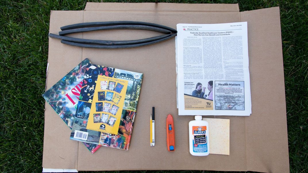 Cardboard on grass with books and papers on top.