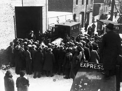 Onlookers watch as police remove the bodies of the victims of an execution-style murder from the scene at 2122 North Clark Street in Chicago.