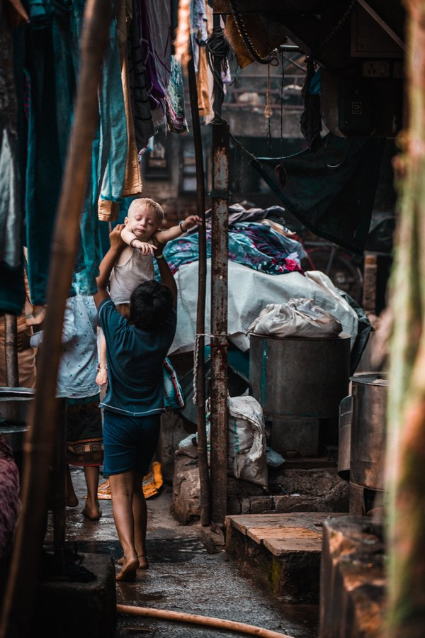 A Indian girl carrying a foster non-Indian boy in the slums of Mumbai. thumbnail