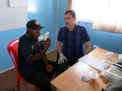 Working with the Papuan Past Project, François-Xavier Ricaut measures the lung function of a highlander study participant at St. Therese's School at Denglagu mission.
