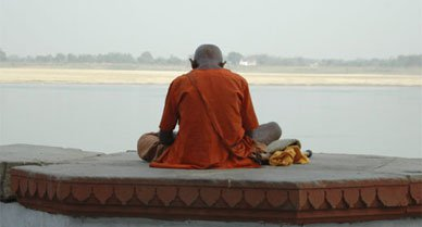 A Hindu monk offers a morning prayer along the Ganges River.