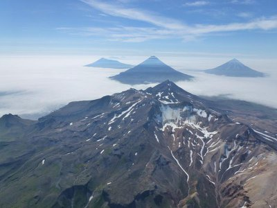 An aerial oblique photo of the volcanoes of the Islands of Four Mountains in Alaska's Aleutian Island chain. In the center is the summit of Mount Tana. Behind Tana are (left to right) Herbert, Cleveland and Carlisle Volcanoes.