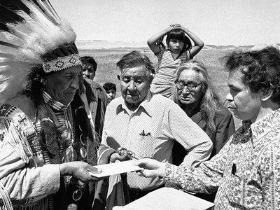 Hank Adams carries a letter from the White House to Chief Frank Fools Crow (Oglala Lakota) during the siege of Wounded Knee. Pine Ridge Reservation, South Dakota, 1973.