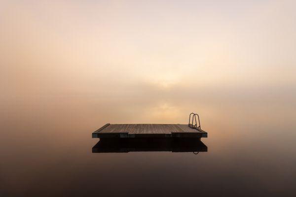 Raft on a dead-calm foggy lake at sunrise thumbnail