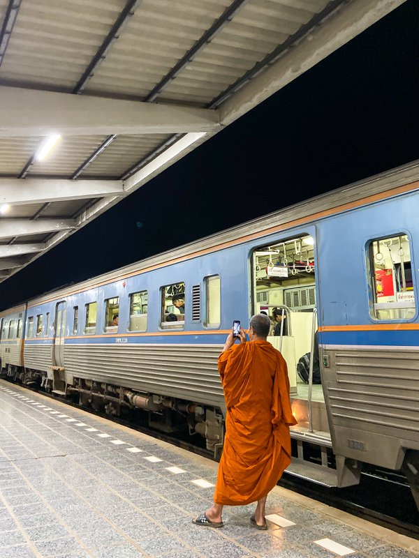 A monk takes a photo of the train and its passengers before departure thumbnail