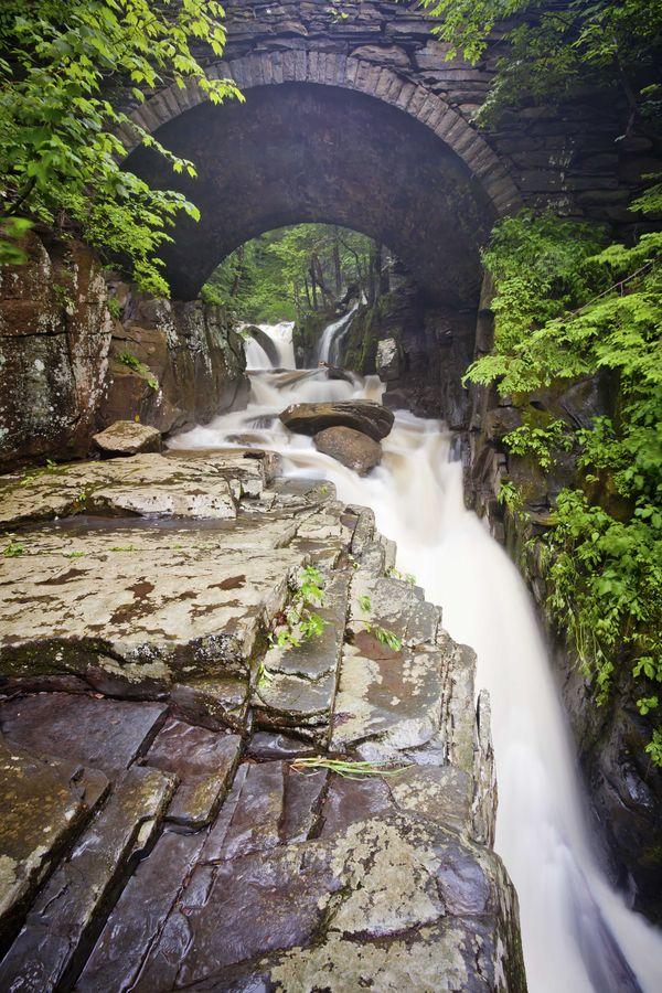 A waterfall runs under a historic stone bridge thumbnail