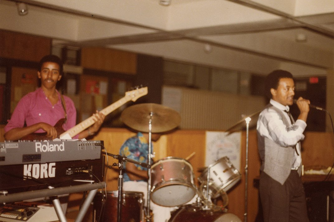 Three band members performing on electric bass, drums, and vocals. Old color film photo.