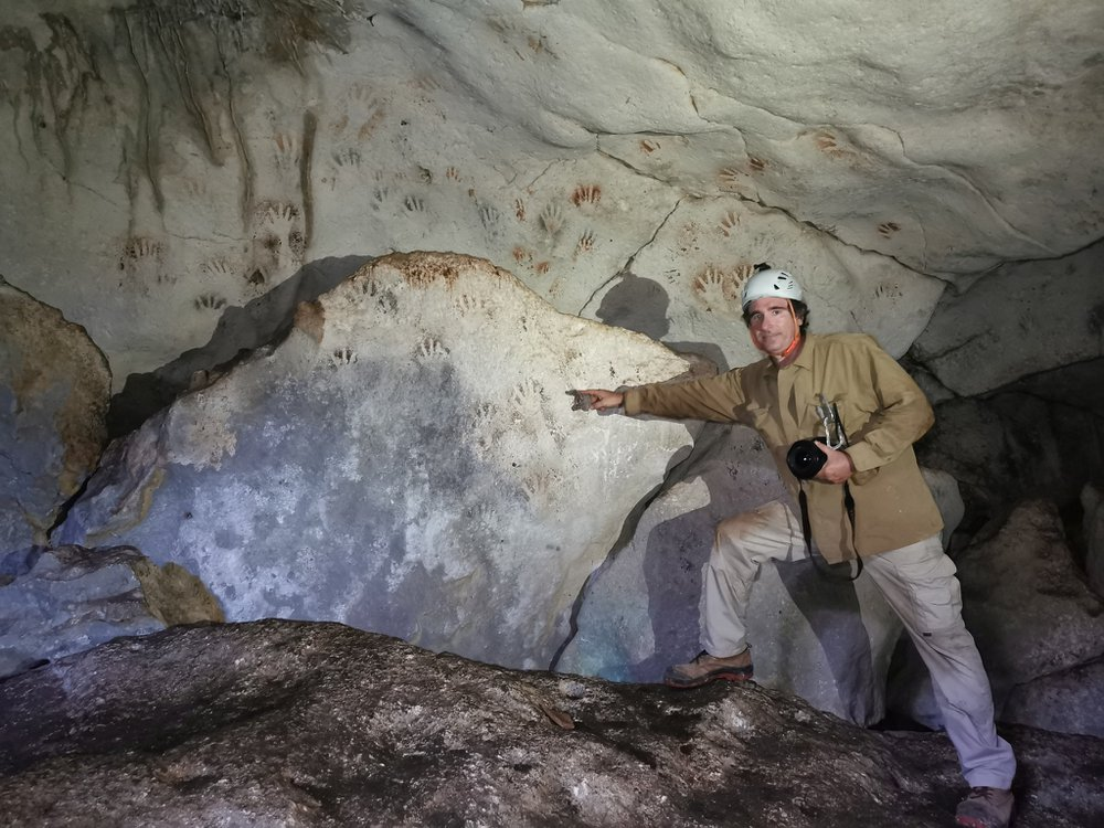 A man wearing boots and a white helmet stands in front of a large rock and points to handprints, which are reddish or white against black shadows and cover the sloping wall of the cave