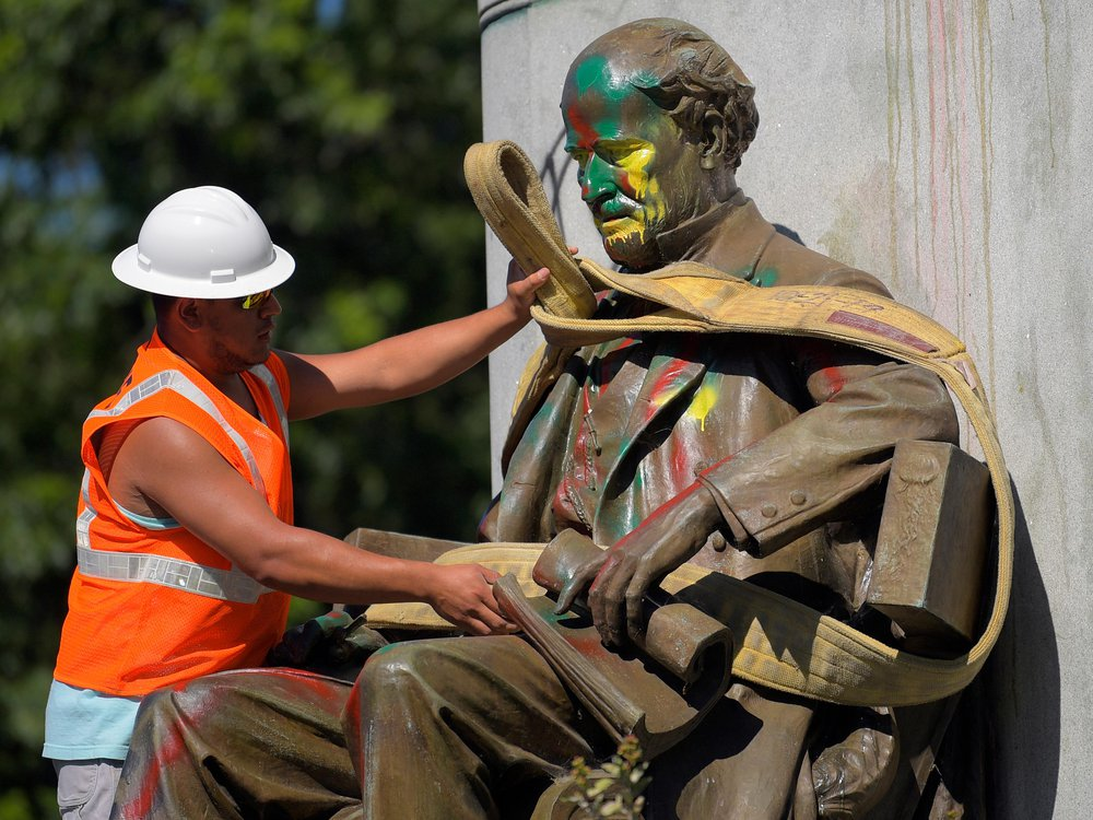 A man in a bright orange construction vest and white hat wraps a thick rope around a paint-splattered statue, of a bearded man wearing a suit and sitting in a chair