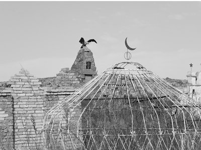 The yurt, a portable, circular hut, has been a part of Central Asian nomadic culture for centuries. During the Soviet era, metal was abundant and cheap, so metallic yurts frequent Kyrgyzstan ancestral cemeteries. An Islamic crescent tops this yurt, and a Kyrgyz hunting eagle spreads its wings in the background.