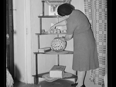 Woman arranging bric-a-brac in her Arizona home circa 1940