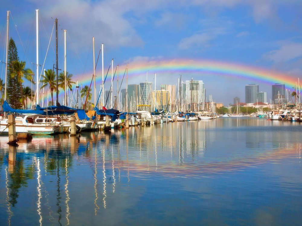 A photo of a rainbow stretching across Honolulu harbor. The photo shows various boats in the water and and a reflection of the rainbow in the water