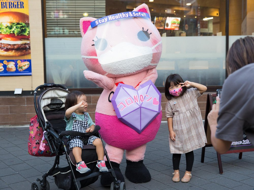 A photo of Japan's Covid-19 awareness Mascot, Koronon, a pink cat with a mask and a purple shield, poses for a photo with two young children.