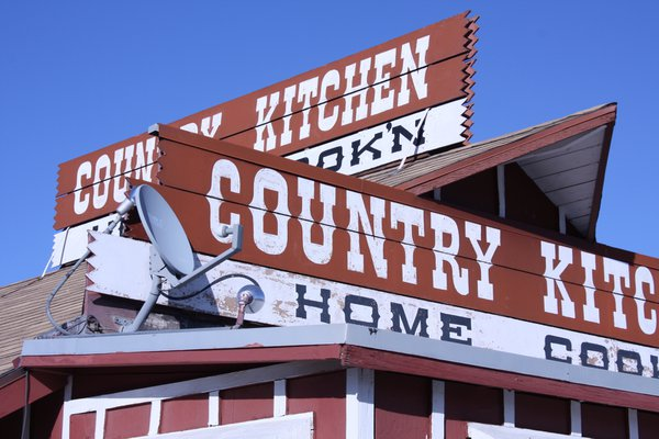 Country Kitchen sign on top of restaurant with satellite dish. thumbnail