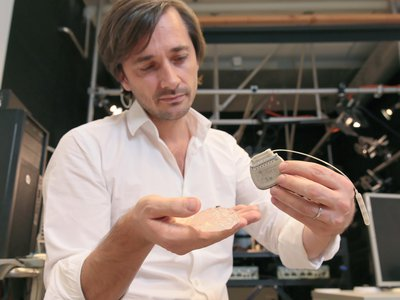 Grégoire Courtine, an author on the new study, holds a silicon model of a primate's brain, a microelectrode array and a pulse generator. The brain-spine interface consists of elements like these.