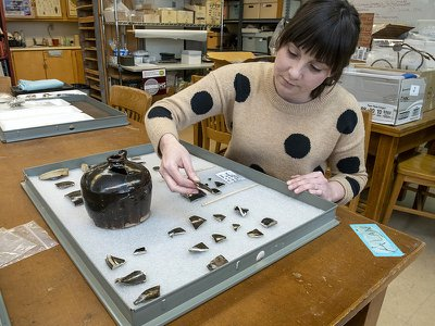 Archaeologist Kate Kolwicz examines fragments of late 19th-century Chinese pottery unearthed in downtown Missoula.