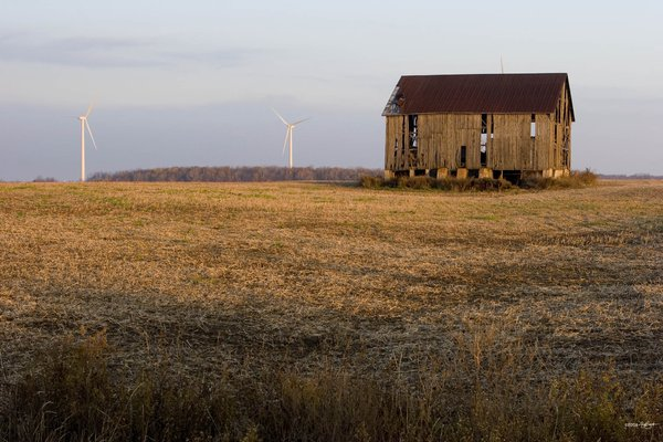 An old barn stands against new wind turbines in the thumb of Michigan. thumbnail