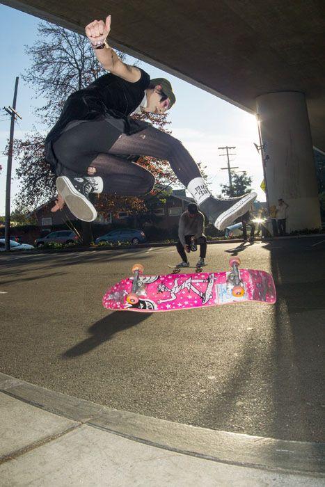 Girl doing kick flip over pink skateboard