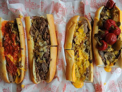 Pat's King of Steaks cheesesteaks (left to right): pizza cheesesteak, steak with provolone and onions, steak with cheez whiz and onions and the steak with mushrooms, onions and cheez whiz topped with hot peppers.
