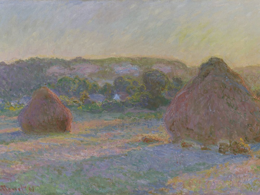 A pinkish field in bluish-yellow light, with one small wheat stack on the left and a larger one, round with a conical top, on the right. It appears to be evening or morning. The stacks leave long purple shadows and the light is hazy