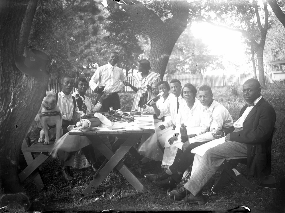 Photograph of ten people and a dog at a picnic table, 1919–1925