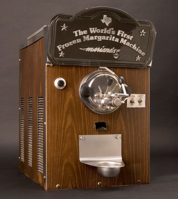 """A margarita machine decorated with faux-wood paneling, metal handles and spigots, and a plaque at the top that reads """"The World's First Frozen Margarita Machine"""""""