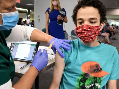 A nurse gives a 16-year-old a Pfizer-BioNTech shot at a clinic in Florida.