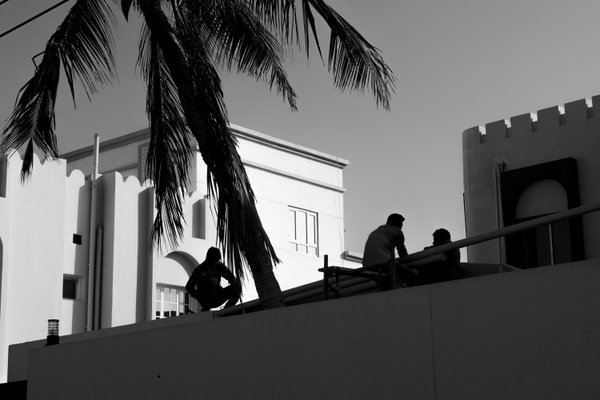 Workers Sit Atop a House in Oman thumbnail