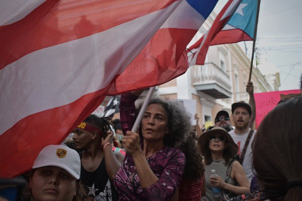 A woman holds the Puerto Rican flag in a protest. thumbnail