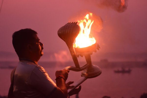 A priest performing morning arti at one of the ghats in Varanasi thumbnail