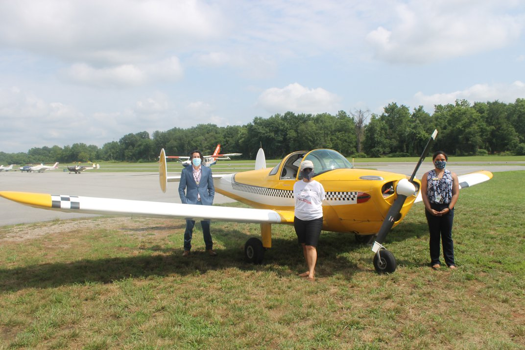 Three people stand in front of a yellow plane.