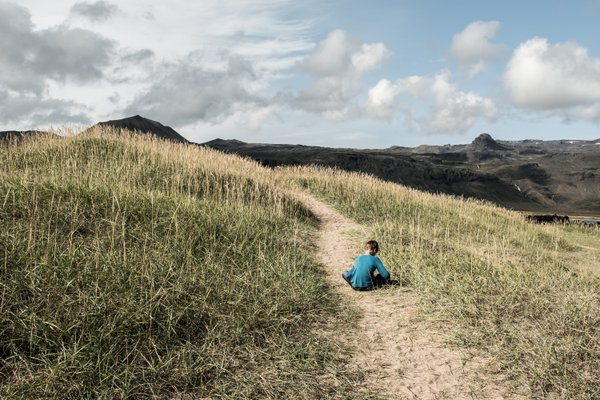 A child plays alone along the sand dunes on the Snaefellsnes Peninsula in Iceland thumbnail