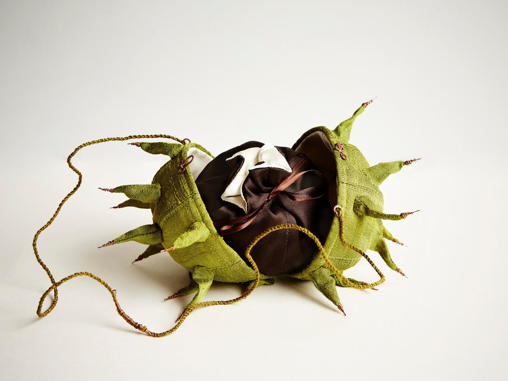 A purse designed to look the like green, spiked outside of a horse chesnut; displayed here, it opens into a small pouch