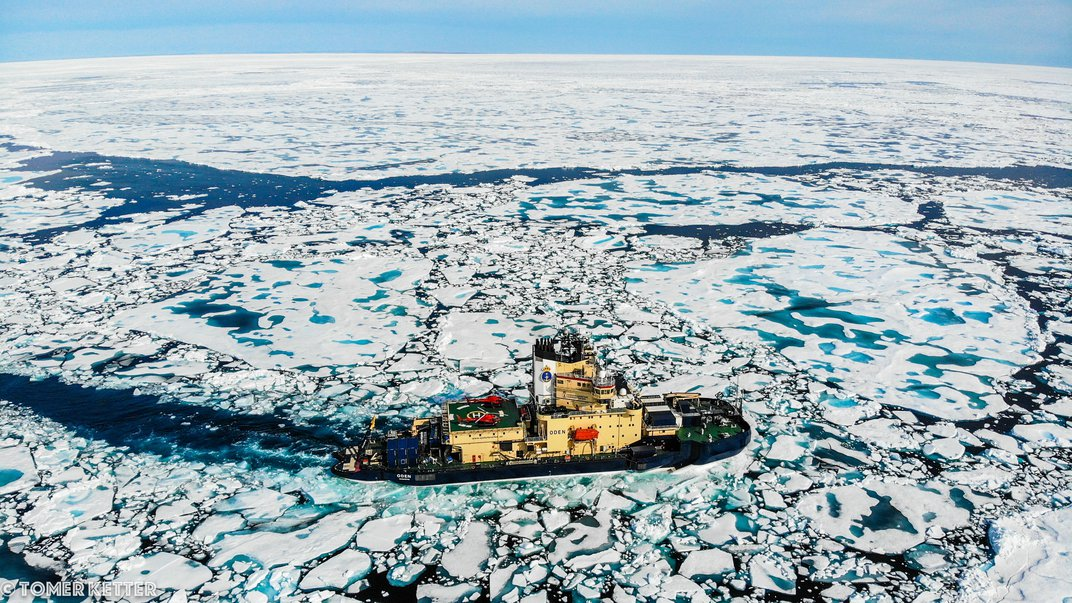 A boat in water with ice sheets floating around it.