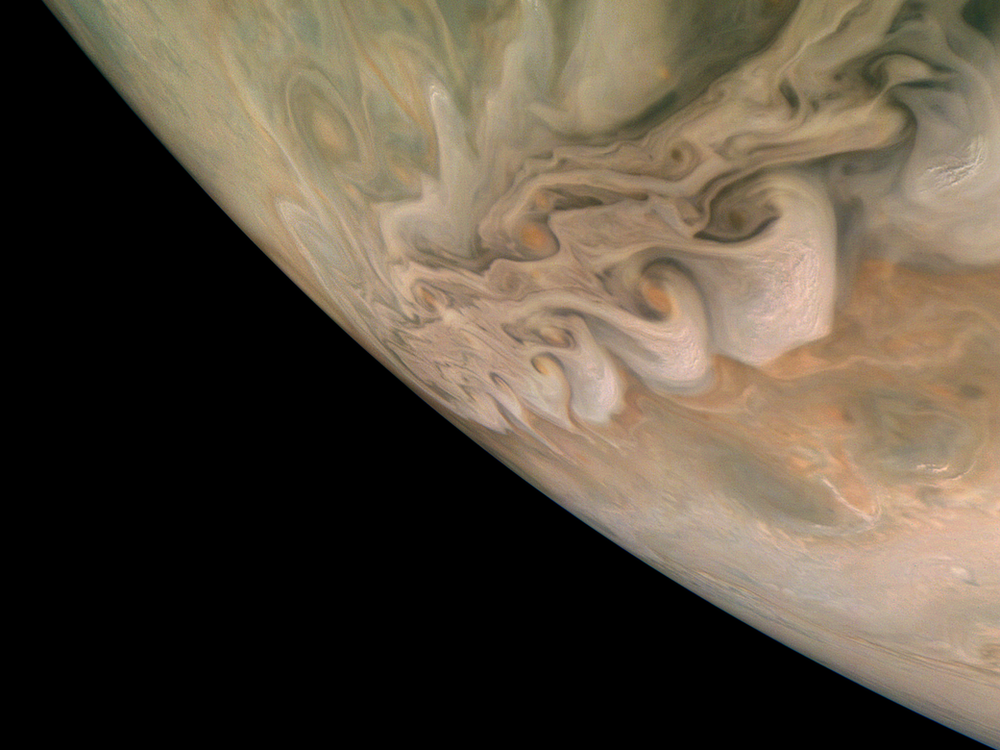 A photograph of Jupiter's swirling clouds and the curve of the planet's horizon
