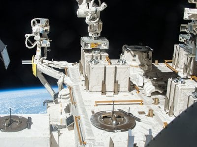 A robotic arm places a container with three panels of bacteria outside the International Space Station.