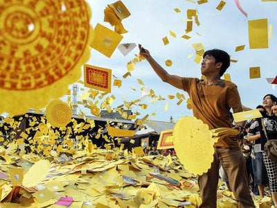 Throwing money into the air during the celebration of the Hungry Ghost Festival.