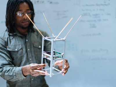 Spire's Austin Ellis shows off a satellite frame at Spire's San Francisco headquarters. Components, like the weather sensor, stack on top of each other inside the frame. Solar panels and antennae fold out from the frame once the device is in orbit.