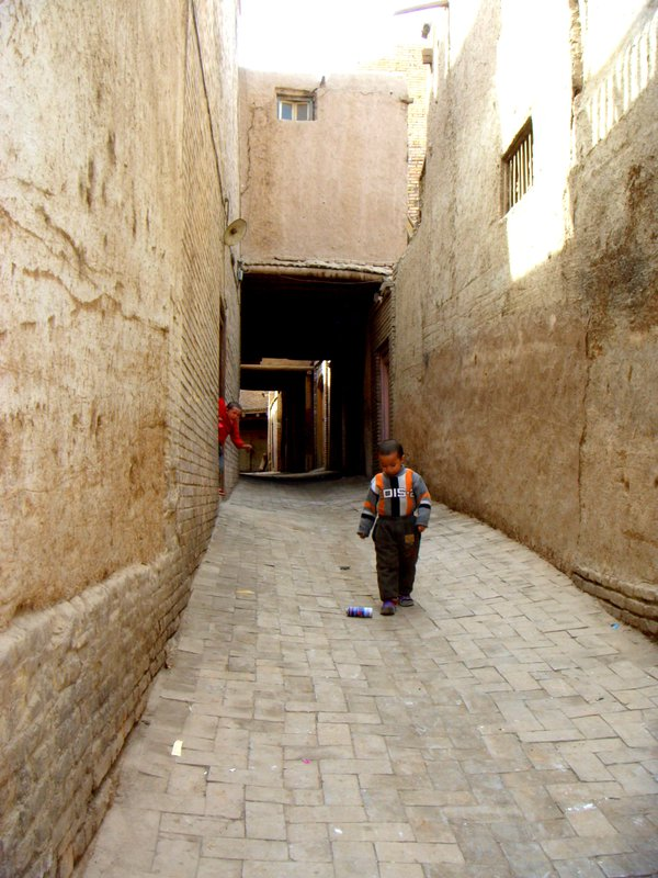 A Uighur child is thrown out of his home as his brother kicks a can in the alley - Kashgar, Xinjiang, China. thumbnail