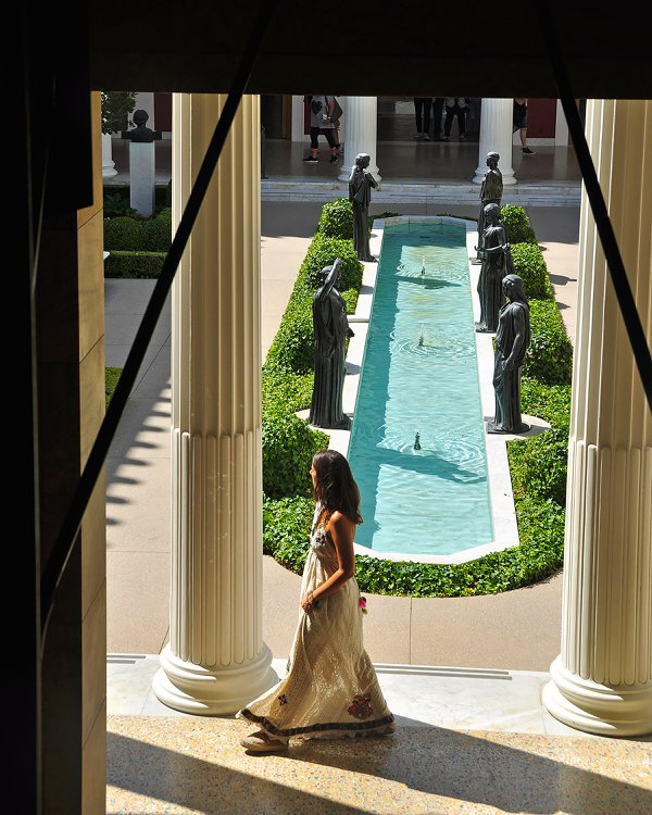 A young woman walks the grounds of the Getty Villa. thumbnail