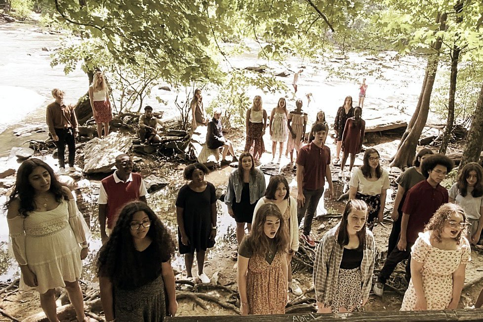 Choir of high school students sing outdoors in dappled sunlight.