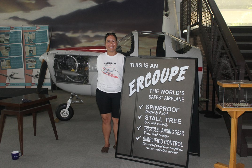 """An armless woman in a white t-shirt stands next to a sign """"Ercoupe"""" with a gray airplane in the background"""