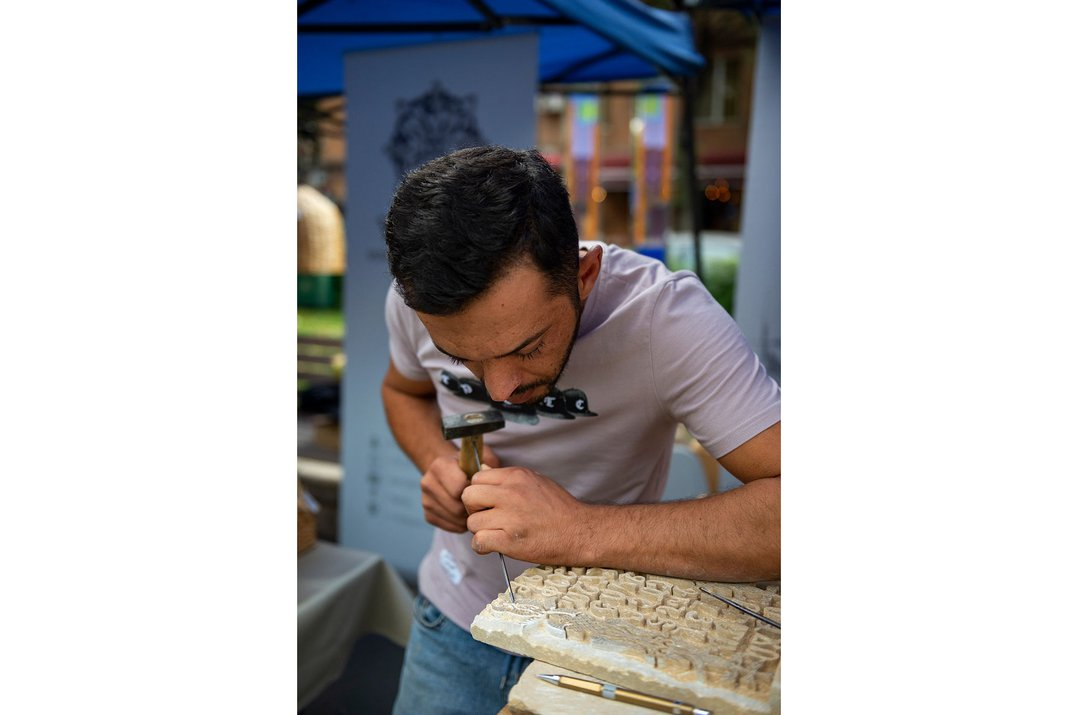 A young man in a blue shirt leans over a table to carve a piece of stone.