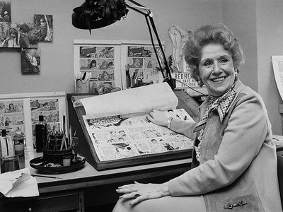 """Dale Messick, creator of the comic strip """"Brenda Starr,"""" looks up from some of her strips in her studio in her Chicago apartment in 1975."""