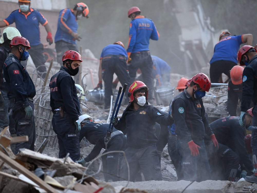 Search and rescue workers in red helmets look through debris for survivors of the October 30 earthquake