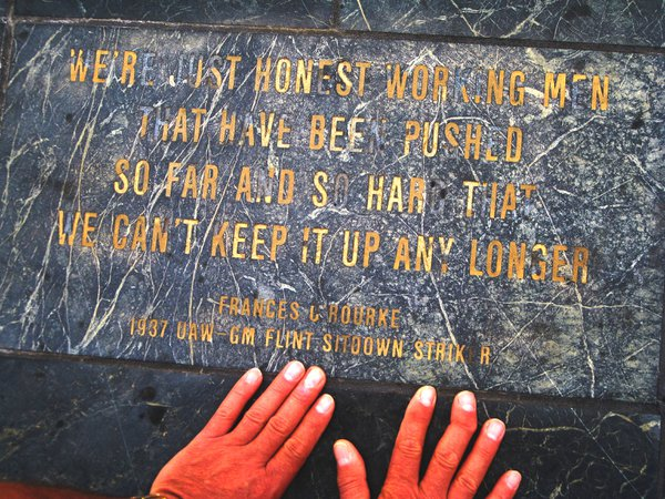 My father, a retired auto worker, placing his hands on the memorial to workers in Hart Plaza - Detroit, Michigan. thumbnail