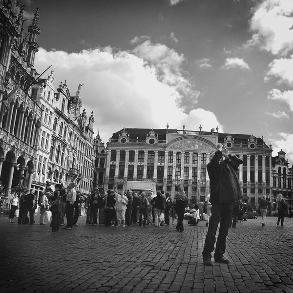 A tourist taking photos of Grand Place in Brussels apart from his group thumbnail