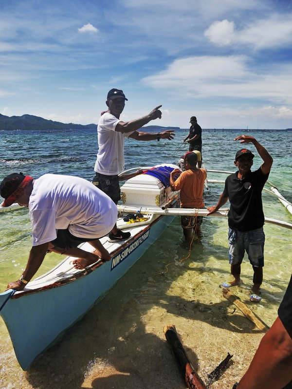 Community leaders prepare and secure a coffin to bring it to a public cemetery three islands away. thumbnail