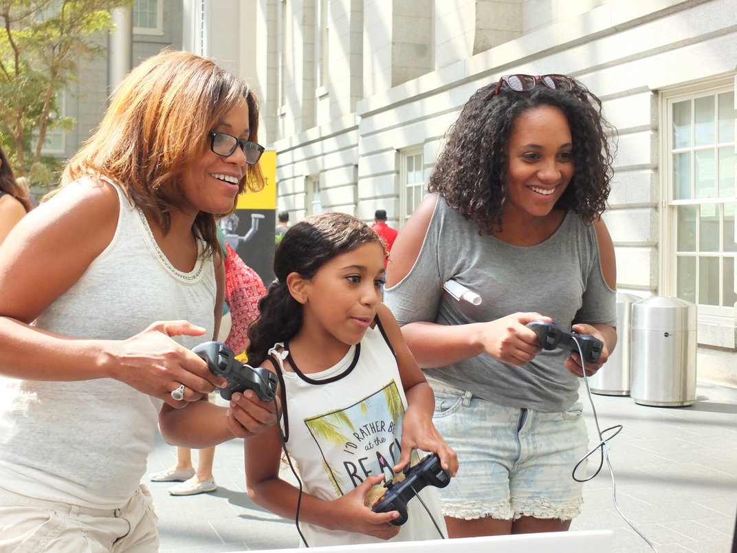 Image of two women and one girl playing video games.